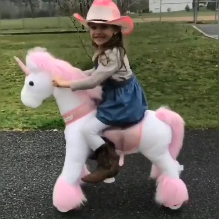 Cow girl with her walking unicorn toy